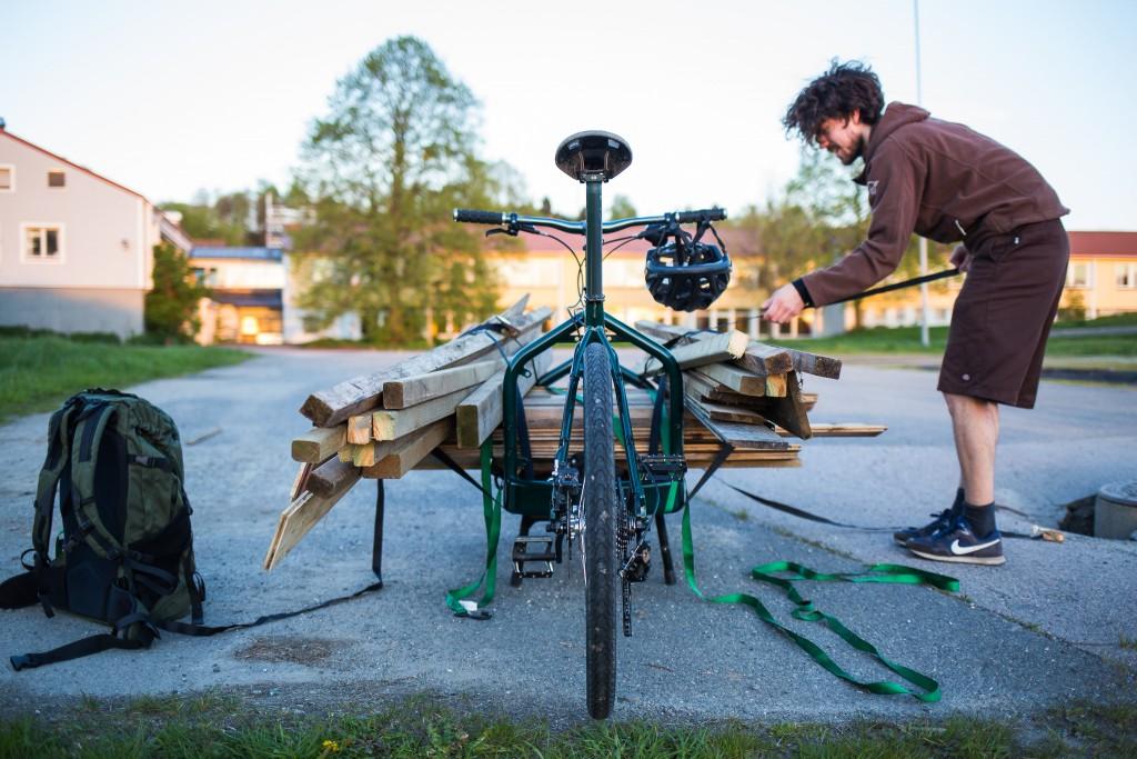 EKSEMPEL: Dette er én av fordelene med en lasteflate uten sidevegger, fotografert utenfor hagegjerdet mitt tidligere i vår. Etter bygging av trehytte ble det en del materialer til overs, som nesten-nabo Arne Sannes Undheim gjerne overtok. Han har ikke bil, men han har Bullitt, og fikset biffen på to hjul. Det var TUNGT, men det gikk. Foto: Geir Anders Rybakken Ørslien