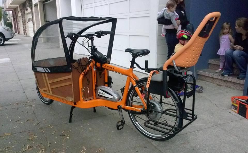 BULLITT. Med Caddyrack bakpå en lastesykkel øker arbeidshest-faktoren realt. Her på en Bullitt, med Yepp-sete oppå bæreren. Lastekassa foran er spesialbygget. Foto: John Lucas – www.cycletrucks.com